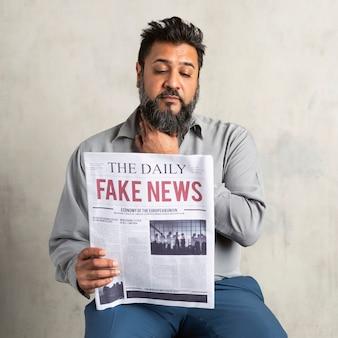 Indiano duvidoso lendo jornal com notícias falsas
