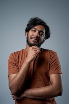 Indiano homem com barba em pose de camisa laranja em fundo cinza, olhando para a câmera e sorrindo.