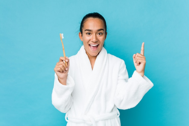 Indiano novo da raça misturada que guarda uma escova de dentes que sorri alegremente apontando com o dedo indicador afastado.