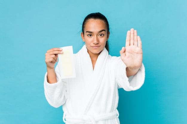 Indiano novo da raça misturada que guarda uma faixa depilatória que está com a mão estendido que mostra o sinal de parada, impedindo-o.