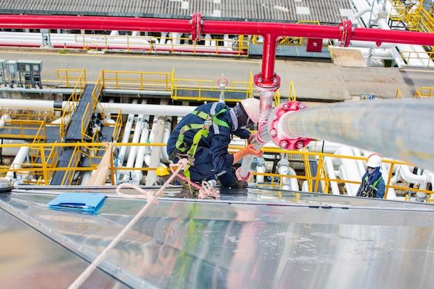 Indicador redondo vermelho de defeito de inspeção de trabalhador masculino e rachadura na água de incêndio de tubulação de equipamento de solda de topo encontrada por teste de penetrante.