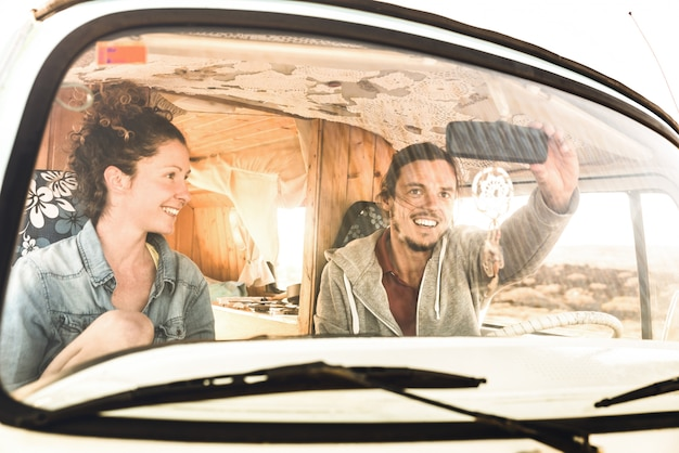 Indie casal pronto para roadtrip no transporte de van mini oldtimer