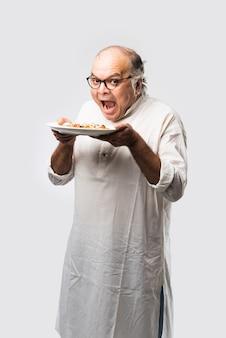 Índio asiático sênior ou idoso comendo pizza em pé, isolado contra uma parede branca