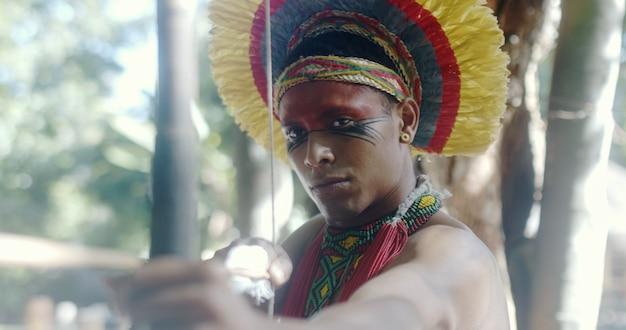 Índio da tribo pataxó com arco e flecha. dia do índio. índio brasileiro