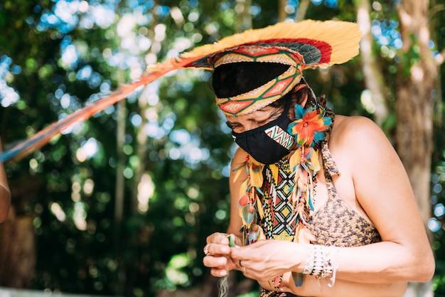 Índio da tribo pataxó com cocar de penas e máscara protetora contra a pandemia covid-19