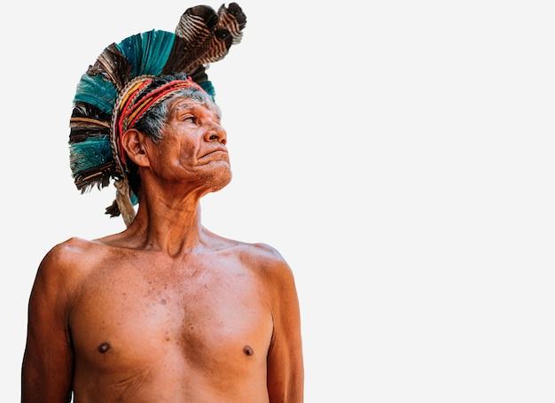 Índio da tribo pataxo com cocar de penas índio brasileiro idoso olhando para a direita