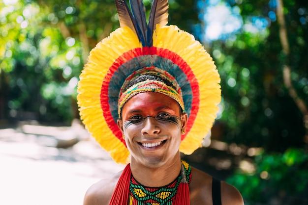 Índio da tribo pataxó com cocar de penas olhando para a câmera
