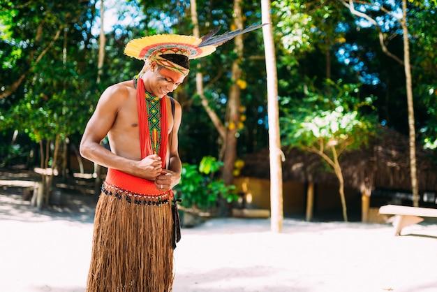 Índio da tribo pataxó com cocar de penas olhando para baixo e sorrindo. indígena do brasil com pinturas faciais tradicionais