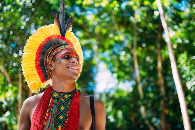 Índio da tribo pataxó com cocar de penas voltado para a direita. indígena do brasil com pinturas faciais tradicionais