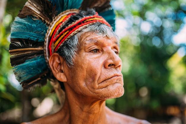 Índio da tribo pataxó, com toucado de penas. índio brasileiro idoso olhando para a direita