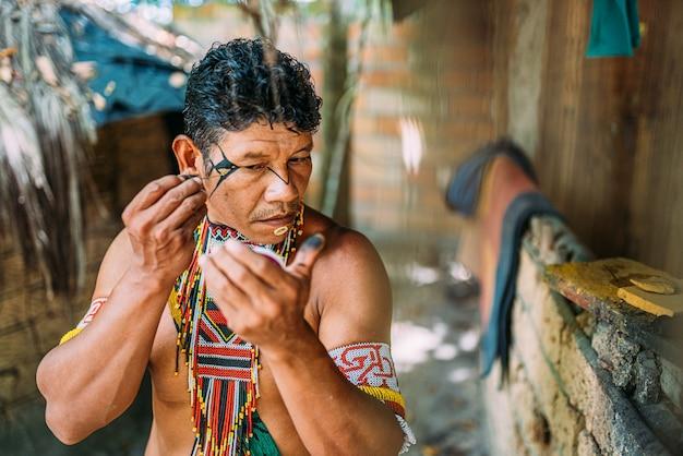 Índio da tribo pataxó, usando espelho e pintando o rosto