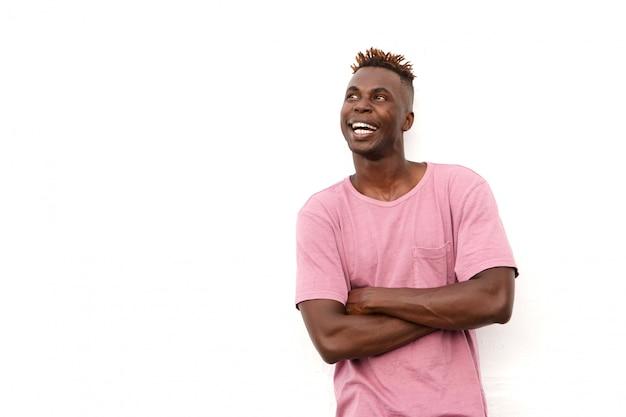 Indivíduo africano de sorriso no t-shirt que olha o espaço da cópia contra o fundo branco