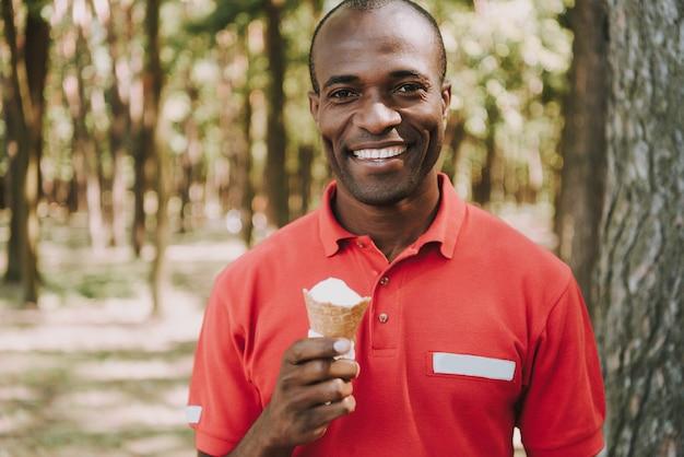 Indivíduo afro-americano está comendo sorvete na floresta.