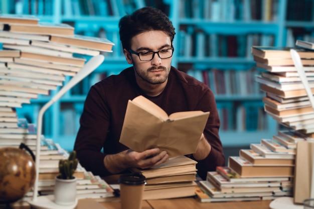 Indivíduo branco que senta-se na tabela cercada por livros na biblioteca.
