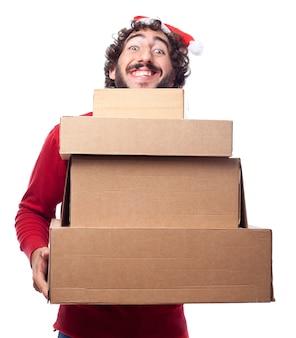 Indivíduo de sorriso com santa caixas de papelão chapéu mostrando