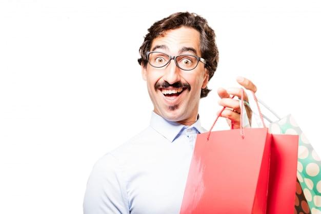 Indivíduo de sorriso que prende sacos de compra coloridos