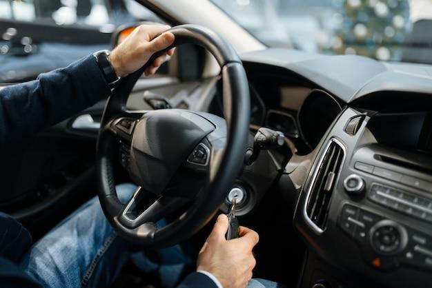 Indivíduo do sexo masculino ao volante de um automóvel novo na concessionária. comprador em showroom de veículos, homem comprando transporte, negociante de automóveis