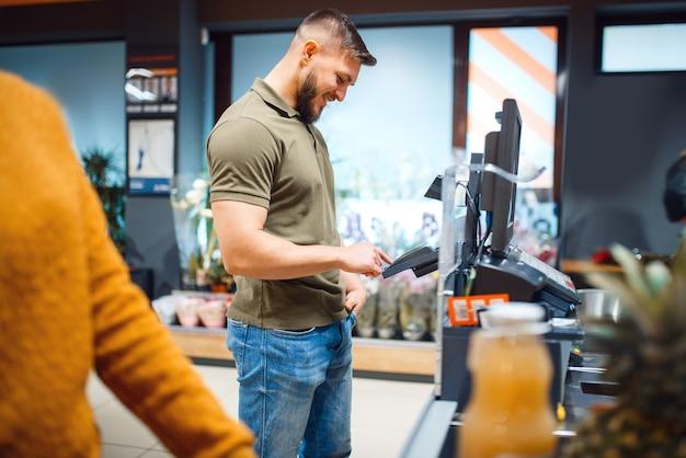 Indivíduo do sexo masculino paga no caixa da mercearia
