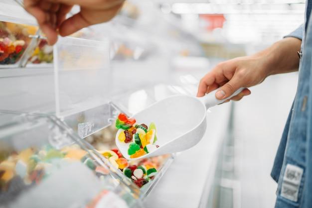 Indivíduo do sexo masculino pega um pacote de doces em borracha em um supermercado, compras da família. cliente compra geleia na loja, comprador no mercado, departamento de doces