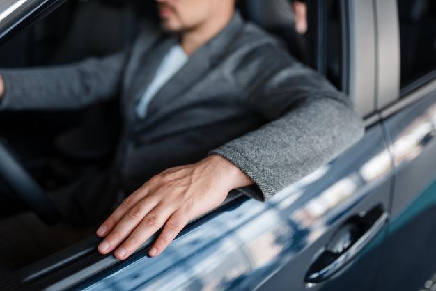 Indivíduo do sexo masculino sentado em um carro novo, showroom.