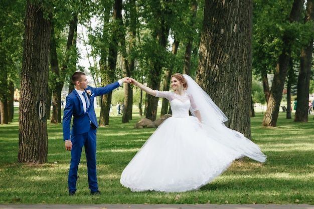 Indivíduo e menina bonitos, noiva em um vestido de casamento branco, noivo em um terno azul clássico contra um fundo da natureza. casamento, criação familiar.