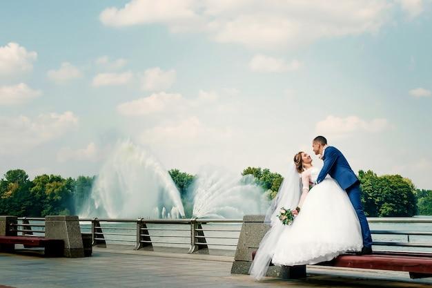 Indivíduo e menina bonitos, noiva em um vestido de casamento branco, noivo em um terno azul clássico contra um fundo da natureza.