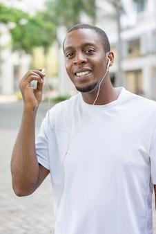 Indivíduo preto feliz no tshirt branco que anda fora com fones de ouvido e que aprecia a música.
