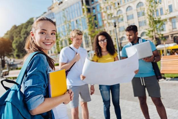 Indo para a universidade. aluna encantada com um sorriso no rosto e segurando o caderno enquanto olha para frente