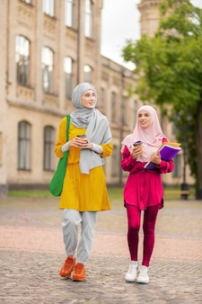 Indo para a universidade. estudantes muçulmanos elegantes indo para a universidade juntos pela manhã
