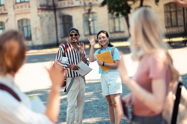 Indo para direções diferentes. dois alunos sorridentes acenando com as mãos para seus colegas de classe em pé na frente do pátio da universidade.