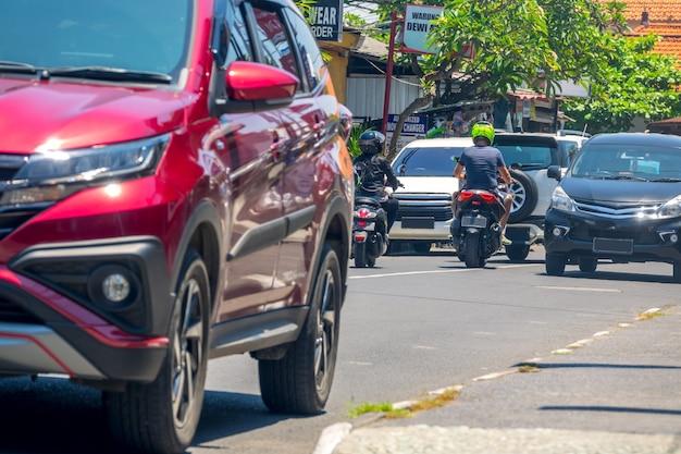 Indonésia. rua da cidade na ilha de bali. dia ensolarado. carros e scooters