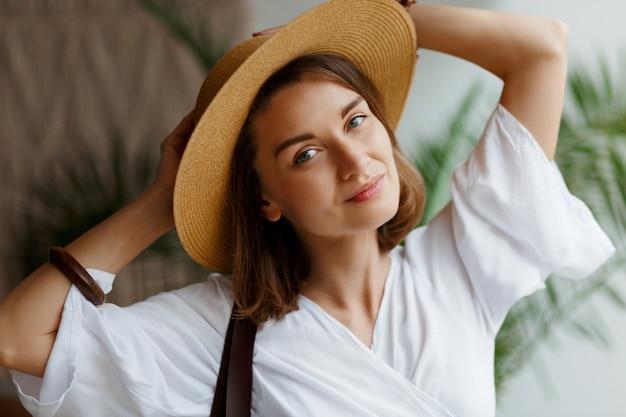 Indoor close-up retrato de mulher bonita elegante com chapéu de palha e vestido branco, posando em casa