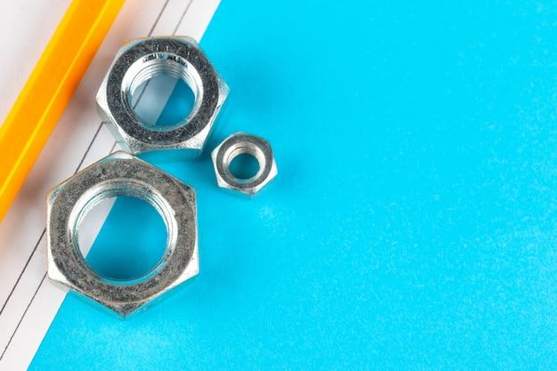 Indústria azul ou construção com várias porcas na superfície azul