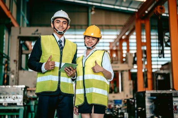 Indústria de engenheiros asiáticos usando capacete de segurança e segurando uma lista de verificação em pé na área da máquina