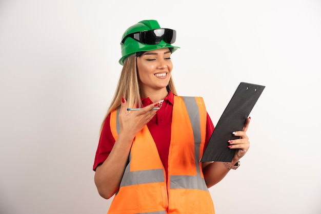 Indústria de mulher trabalhador retrato vestindo uniforme de segurança e óculos de proteção em pé sobre fundo branco. Foto gratuita