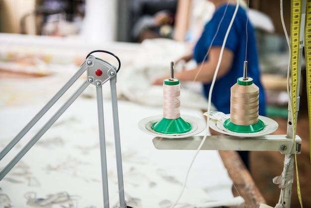 Indústria de roupas. linhas na máquina de costura, ferramentas e acessórios na oficina de costura.