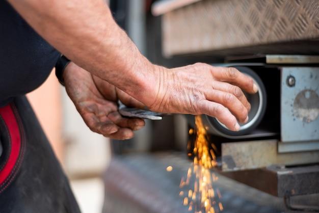 Indústria metalúrgica: acabamento de metal que trabalha na máquina de moedor de superfície horizontal
