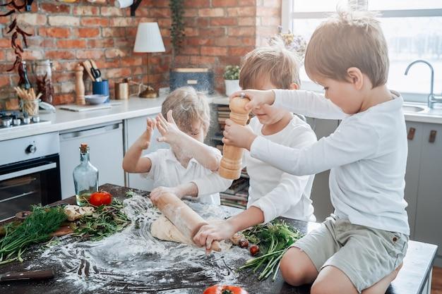 Infância e atividade de lazer em casa. três meninos em idade pré-escolar brincam juntos, aprendendo a cozinhar na cozinha durante o dia.
