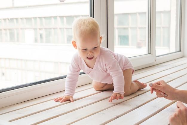 Infância, família e conceito infantil - bebezinho no peitoril da janela em casa