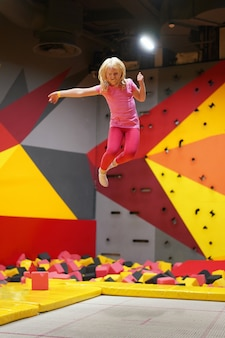Infância feliz de uma criança moderna na cidade - menina pulando no parque de trampolim