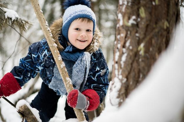 Infância feliz - menino alegre escalando uma árvore em um bosque nevado no inverno