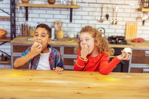 Infância feliz. menino faminto olhando para a câmera enquanto morde um bolo saboroso