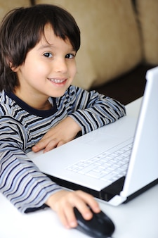 Infância, laptop, aprendendo e jogando