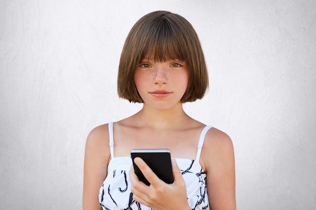 Infância na era digital. linda garota com penteado curto e elegante, olhos profundos escuros e sardas com belo vestido, segurando o telefone inteligente nas mãos, jogando jogos online isolados na parede branca