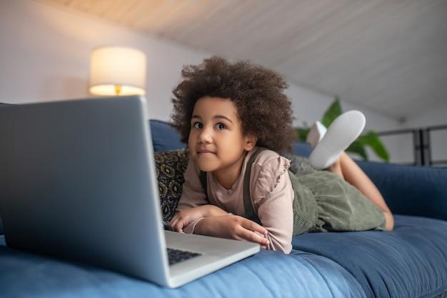 Infância, passatempo. menina afro-americana pensativa deitada no sofá em casa na frente do laptop