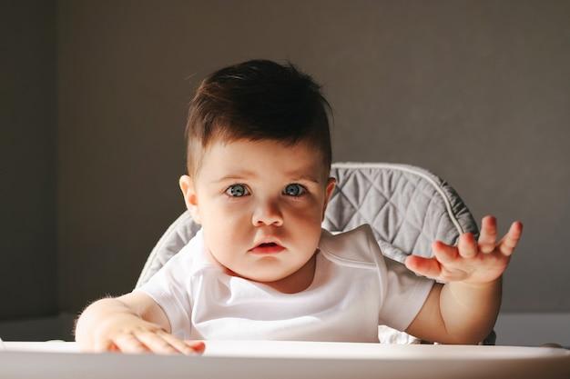 Infeliz criança sentada em sua cadeira comendo. criança triste e infeliz na cadeira pequena. menino chateado de manhã cedo