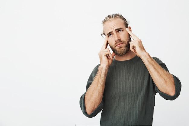 Infeliz homem bonito com um bom penteado e barba, sentindo-se extremamente cansado, segurando o dedo na testa