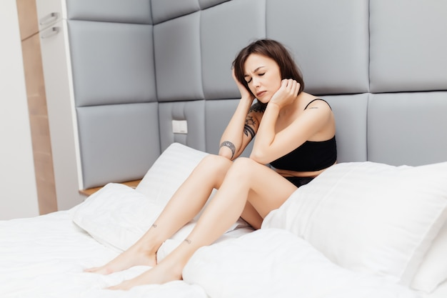 Infeliz mulher morena cansada, acordando de manhã na cama dela