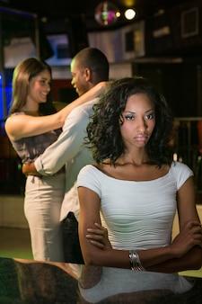Infeliz mulher sentada no balcão de bar e casal dançando atrás dela no bar