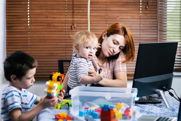 Infelizmente, mãe jovem está tentando trabalhar em um computador em um trabalho remoto durante o período de auto-isolamento em conexão